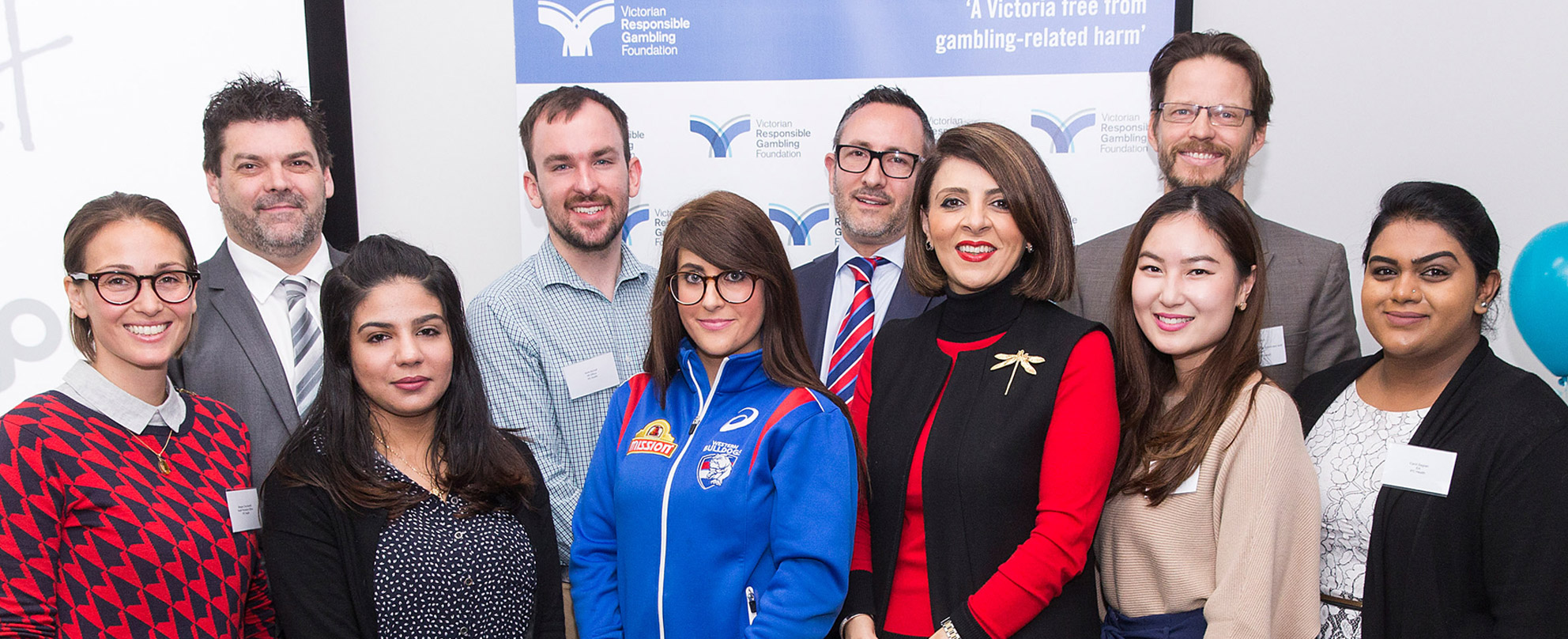 Minister Marlene Kairouz (third from right, front), Catherine Dell'Aquila (Sons of the West, fourth from right, front), Nathan Villiers (Brimbank City Council, first right, back), Alex Johnstone (CEO of IPC Health, second from right, back) and Craig Swift (Acting CEO of the Victorian Responsible Gambling Foundation, first left, back) with IPC Health staff at the launch of the 14 prevention projects, photo: Paul Jeffers