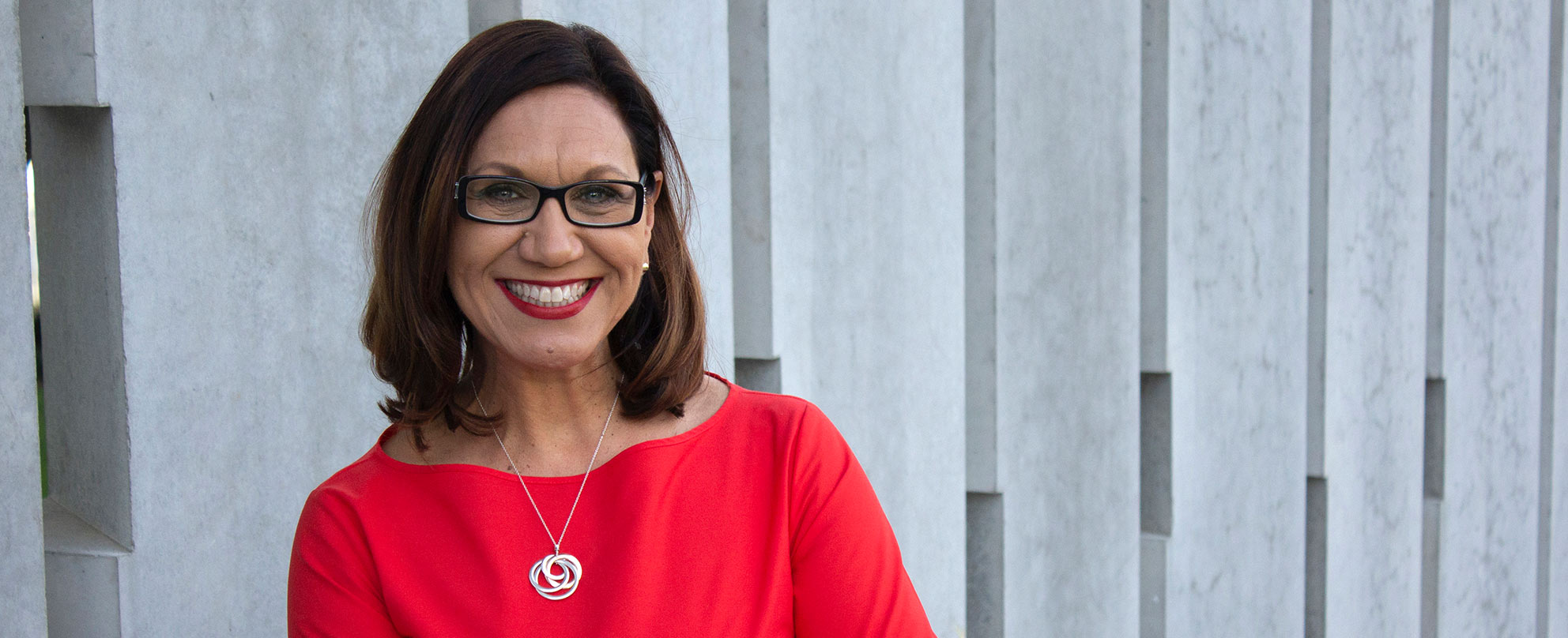 Photo of a middle-aged woman with a brown bob and dark-rimmed glasses, wearing a bright red top and matching lipstick, smiling broadly, a wall of concrete columns directly behind her.